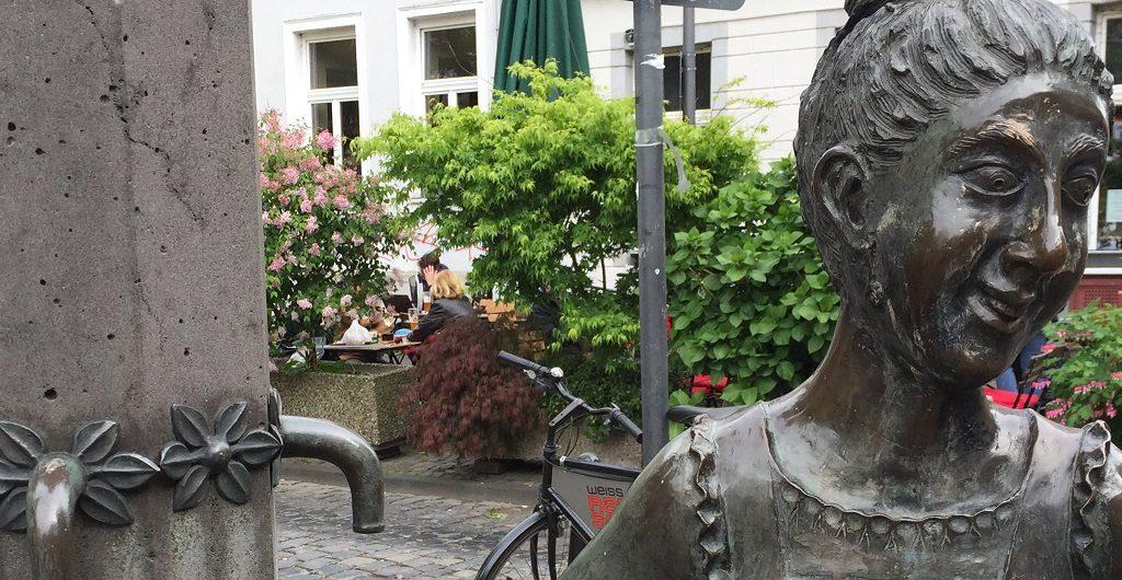 "Brunnen und Skulptur ""Schokoladenmädchen"" in der Nähe vom Vringstreff (Foto: Jutta Eggeling)"