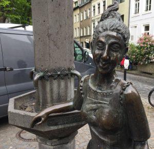 """Brunnen und Skulptur """"Schokoladenmädchen"""" auf dem Severinskirchplatz in Köln"""