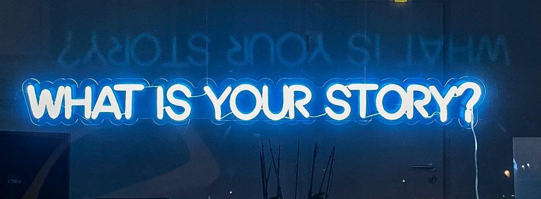 """Foto versinnbildlicht mit der Neonschrift """"What is your story?"""" die Stimmen zu Housing First Köln"""